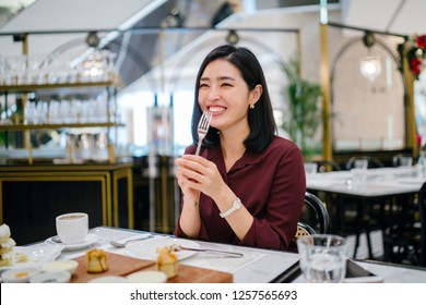 A beautiful, elegant Korean Asian woman laughs and smiles as she enjoys cake with her fork and talks to her close friend as they sit in a cafe on the weekend.