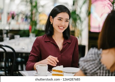 A beautiful and elegant Korean Asian woman is enjoying tea and cake with with her best friend in a cafe on the weekend. She is smiling and laughing as she talks to her friend.