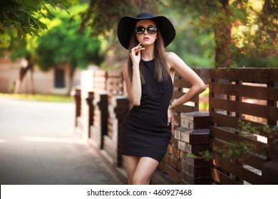Beautiful elegant lady in hat and little black dress outside.