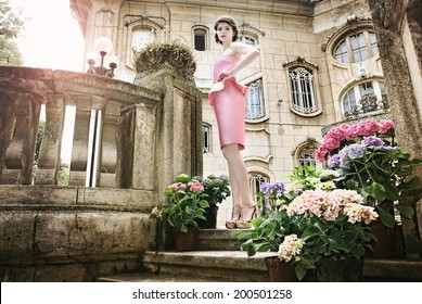 Beautiful elegant lady, in haute couture dress, posing in front of mansion . She might also be there waiting for her lover, guests, for private party etc.