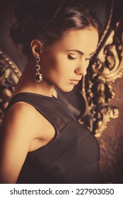 Beautiful elegant lady stands by the mirror in vintage interior. Fashion shot.