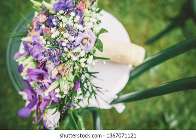 Beautiful elegant lilac summer wedding bouquet on a green chair close up image