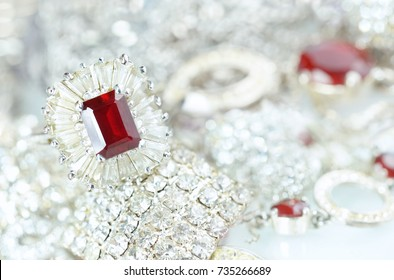 Beautiful elegant luxury composition of from silver and platinum jewelry with with rings and a big ruby gemstone and diamonds on light silvery background close-up macro.