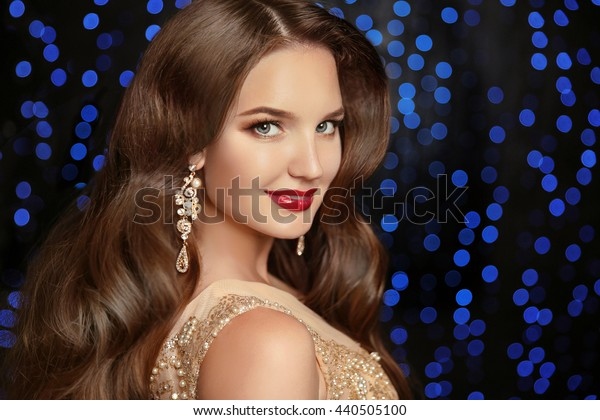 Beautiful elegant model brunette with long wavy hair and jewelry earrings isolated on holiday blue party lights background.
