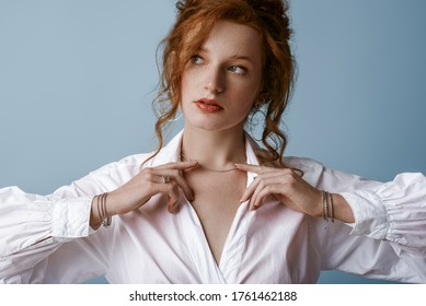 Beautiful elegant redhead freckled woman wearing luxury silver jewelry: earrings, chain, bracelets, white shirt, posing in studio, on blue background. Jewellery advertising concept. Close up portrait