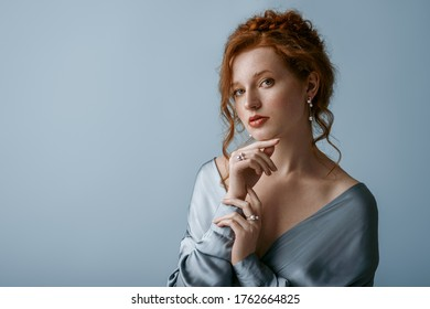Beautiful elegant redhead freckled woman wearing luxury pearl jewelry: earrings, rings, silk blouse, posing in studio, on blue background. Jewellery advertising conception. Copy, empty space for text