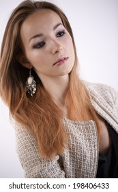 Beautiful elegant redhead woman with long hair in a stylish jacket and earrings gazing into the distance with a serious pensive expression