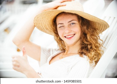 Beautiful ,elegant, teenager, with red hair and freckles,wearing a white dress and a hat, enjoy the seaside resort, sunny day on the beach, she winks,and smiles.