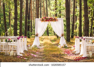 Beautiful elegant wedding decorations of place for ceremony outside in old wood with huge pines trees. Horizontal color photography.