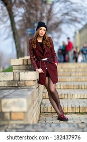 Beautiful elegant woman in autumn clothes at the stairs