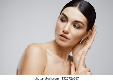 Beautiful elegant woman with bare shoulders on a gray background Cosmetology Clean skin