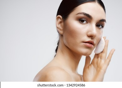 A beautiful elegant woman with bare shoulders with a cotton disc wipes her face clean skin