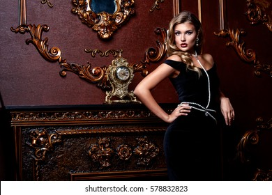 Beautiful elegant woman in black dress and jewelery of pearls is standing by a fireplace in a luxury apartment. Classic vintage interior. Beauty, fashion.