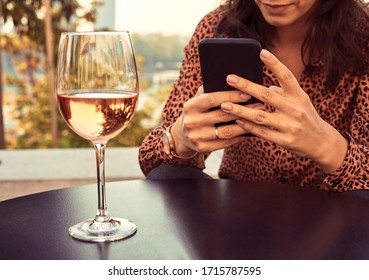 Beautiful elegant woman drinking wine and using cellphone outdoors.