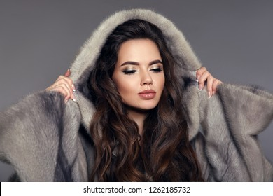 Beautiful elegant woman with hood in mink fur coat isolated on gray studio background. Fashion Brunette Girl in Luxury Winter outerwear.