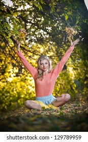 Beautiful elegant woman with long legs in autumn park .Young pretty woman at the autumn park. Beautiful woman spending time in park during autumn season .Young pretty woman at the autumn park
