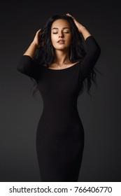 Beautiful elegant woman with longs hair posing in classy black dress holding hands on head sensually.