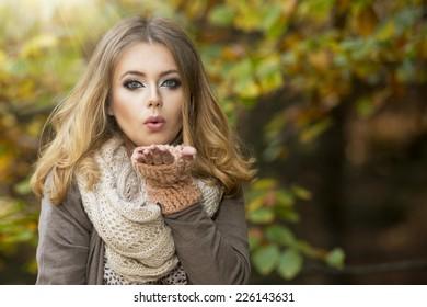 Beautiful elegant woman  in a park in autumn send kiss