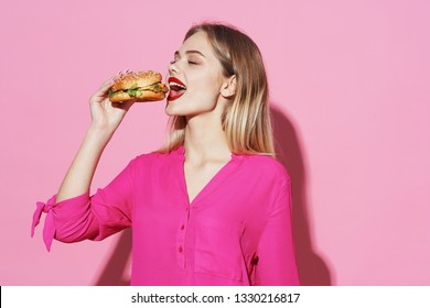Beautiful elegant woman in a pink shirt eating a hamburger on a pink background Fastfood