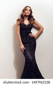 Beautiful elegant woman posing in black maxi dress, looking at camera.