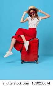 A beautiful elegant woman in a red skirt is sitting on a red suitcase with glasses and a hat over a blue background