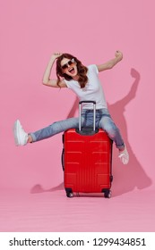 Beautiful elegant woman with a red suitcase for travel on a pink isolated background with travel sunglasses