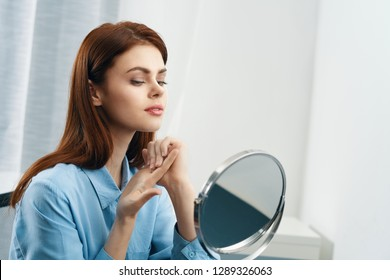 Beautiful elegant woman sitting at a table in a blue shirt in front of a mirror