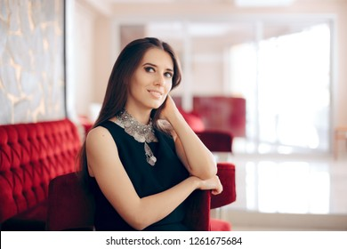 Beautiful Elegant Woman Waiting in Hotel Lobby. Sophisticated fashion girl wearing Turkish style statement necklace