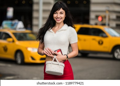 Beautiful elegant woman waiting for yellow taxi on city street of New York