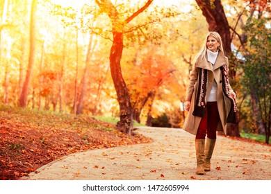 Beautiful elegant woman walking  through the a park in autumn , Fall concept