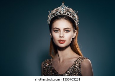 beautiful elegant woman wearing a gold dress with a crown on her head makeup on her face model appearance celebrity dark background