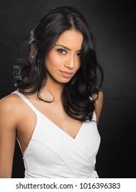 Beautiful elegant woman wearing white dress against black background