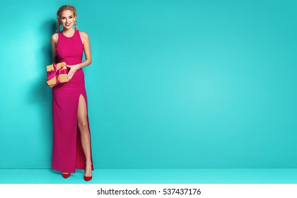 Beautiful elegant young blonde woman in pink dress sitting on a big present, holding gift box. Christmas photo, presents