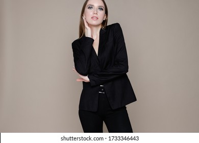 Beautiful elegant young girl in black suit with evening make-up posing on gray background. Concept of stylish clothes and advertising of womens goods and discounts in online store. Place for text