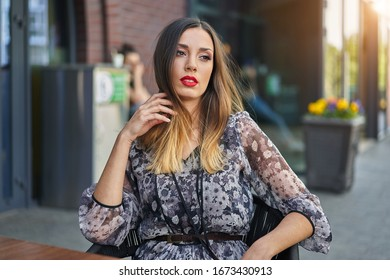 Beautiful elegant young girl with dark dyed long hair sits at a table summer outdoor cafe waiting for her boyfriend. European woman resting after shopping. Free space for text