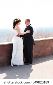 Beautiful elegant young wedding couple is embracing at top of hill with picturesque amazing view at summer bright sky