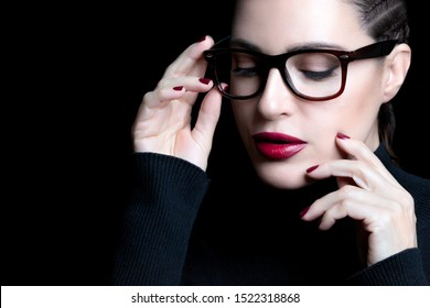 Beautiful elegant young woman with braided hair wearing glasses or spectacles looking down with hand to the frame in a vision correction, optometry and fashion eyewear concept on black background