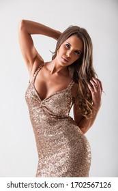 Beautiful elegant young woman in fashionable golden evening dress