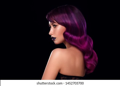 Beautiful elegant young woman with Hollywood wave hair. Portrait attractive charming girl with big curls and colored purple hair. Salon of smooth hair. Long wavy hair, Look away, black background