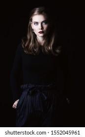 Beautiful elegant young woman posing at studio over black background.