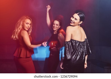 Beautiful elegantly dressed female friends have fun at the nightclub