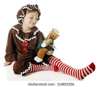 "A beautiful elementary ""gingerbread girl"" admiring her gingerbread doll.  On a white background."