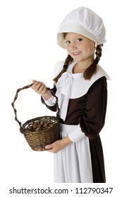 A beautiful elementary Pilgrim displaying her basketful of acorns.  On a white background.