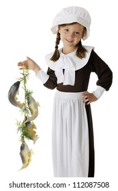A beautiful, elementary Pilgrim girl happily displaying the colony's catch of fish, a likely food for the first Thanksgiving feast.  On a white background.