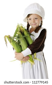 A beautiful elementary Pilgrim girl happily carrying an armload of fresh corn.  On a white background.