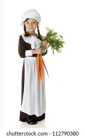 A beautiful elementary Pilgrim girl holding a bunch of fresh carrots.  On a white background.