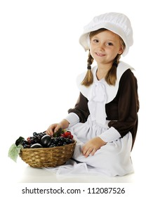 A beautiful elementary Pilgrim girl sitting with a basketful of fruit.  On a white background.