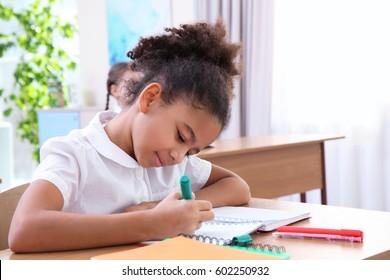 Beautiful elementary schoolgirl studying in classroom