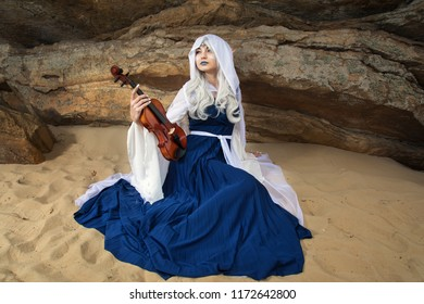 A beautiful elf girl playing the violin among the stones and sands