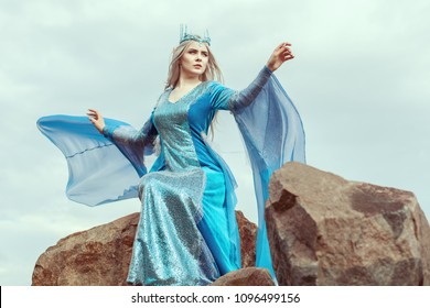 Beautiful elf woman in blue dress sits on top of a mountain.